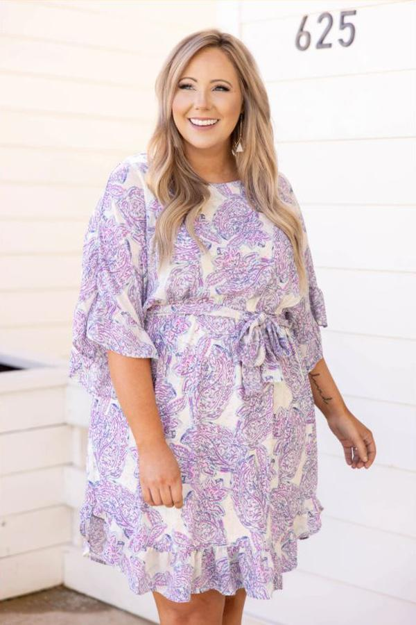 a full figured woman modelling a showed up to the party dress in blue lavender